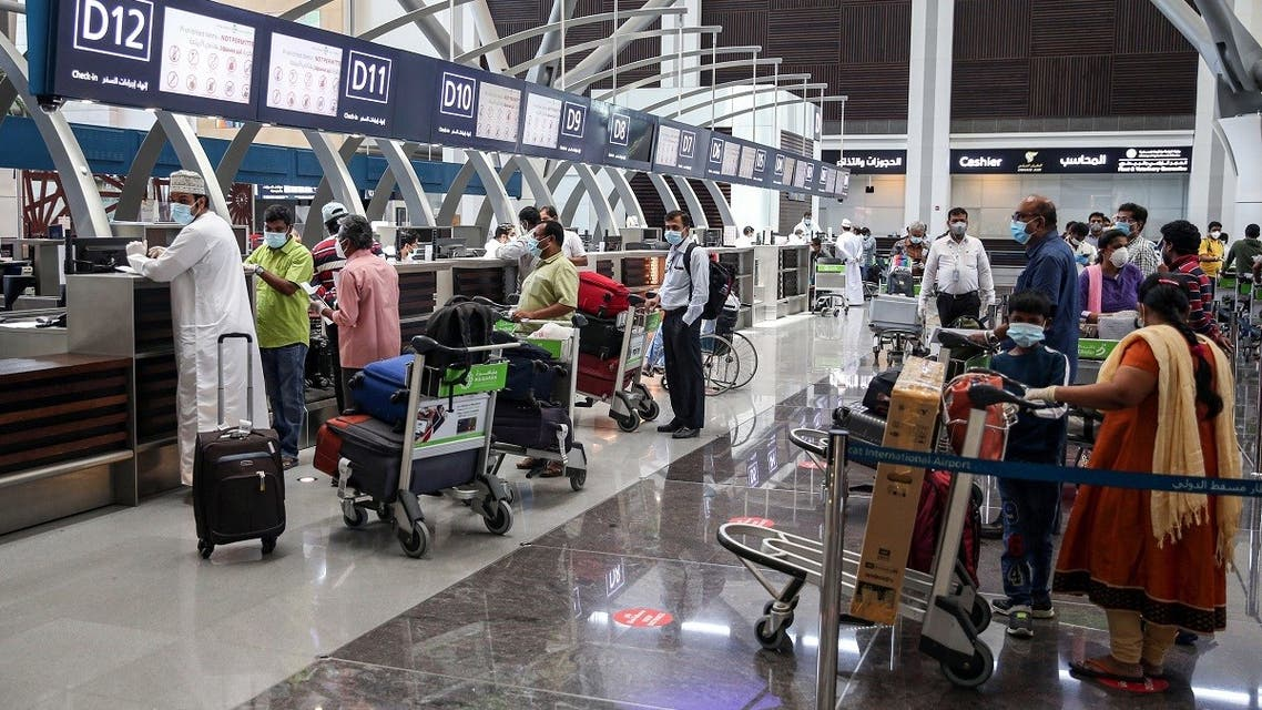 Indian nationals residing in Oman, wearing face masks due to the COVID-19 coronavirus pandemic, queue with their luggage at the check-in counter at a terminal in Muscat International Airport ahead of their repatriation flight from the Omani capital, on May 12, 2020. (AFP)