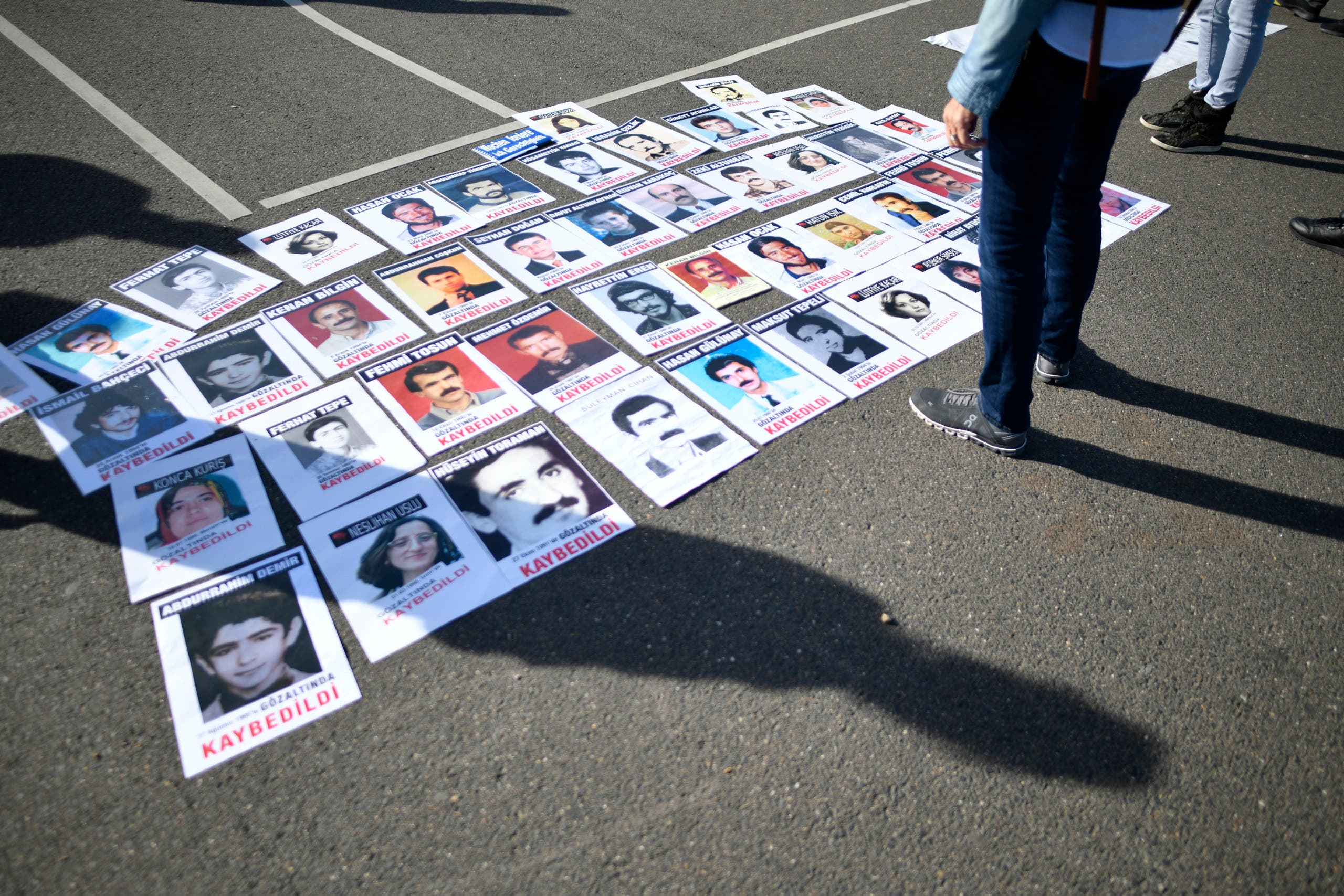 Photos of Turkish people who died in jail in Turkey lay on the ground during a demonstration in Cologne prior to the visit of the Turkish President to Cologne, on September 29, 2018. (AFP)