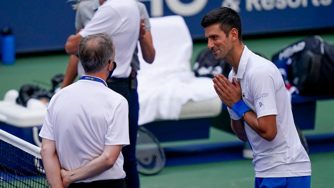 Novak Djokovic, of Serbia, talks with the umpire after inadvertently hitting a line judge with a ball after hitting it in reaction to losing a point against Pablo Carreno Busta. (AP)