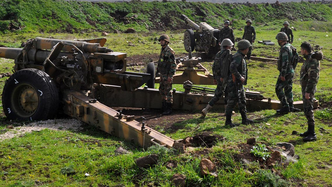 Syrian government forces stand near an artillery gun as they take position in the area between Talbiseh and Rastan in the northern countryside of Homs on March 1, 2018.