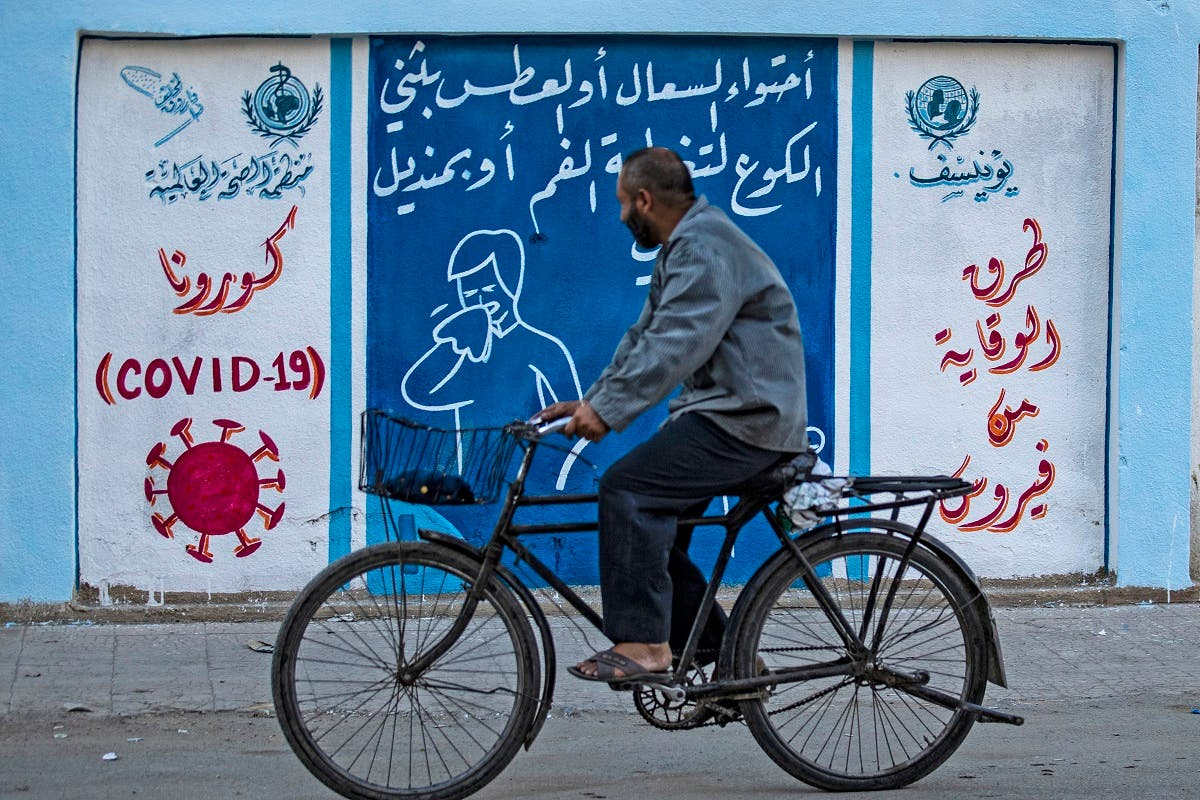 A Syrian man rides a bicycle past a mural painted as part of an awareness campaign by the United Nations International Children's Emergency Fund (UNICEF) and World Health Organization (WHO) initiative on coronavirus in Qamishli, Syria, August 16, 2020. (AFP)