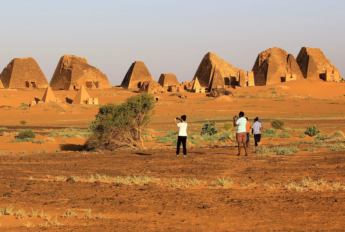 Tourists take pictures of the Royal Cemeteries of Meroe Pyramids in Begrawiya at River Nile State. (Reuters)