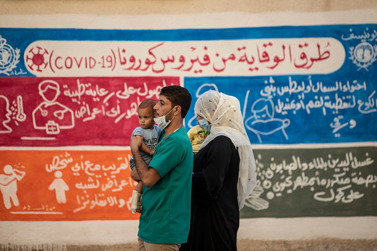 A Syrian family walks past a mural painted as part of an awareness campaign on coronavirus  by the United Nations International Children's Emergency Fund (UNICEF) and World Health Organization (WHO) in Qamishli, Syria, August 16, 2020. (AFP)