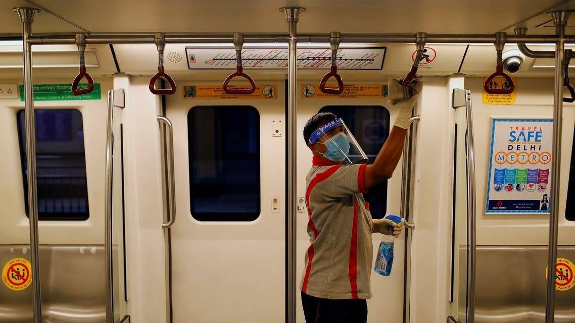 A worker sanitizes the interior of  the Delhi Metro  coach before it resumes operation. (Reuters)