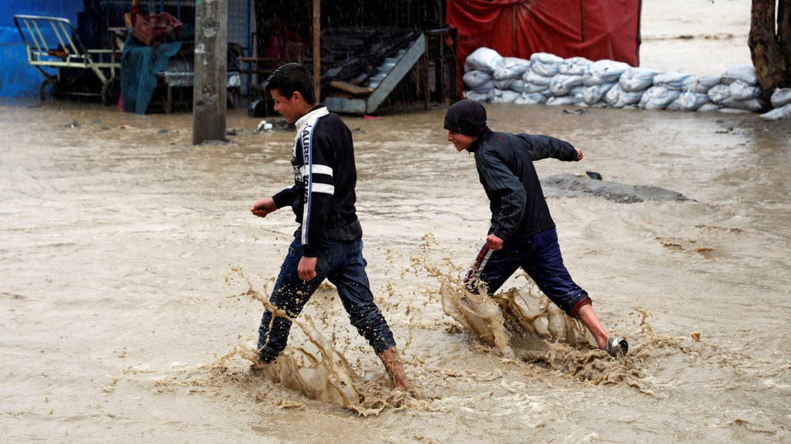 Afghan boys walk through flood waters on a street as heavy rain falls in Kabul, Afghanistan April 16, 2019. (Reuters)