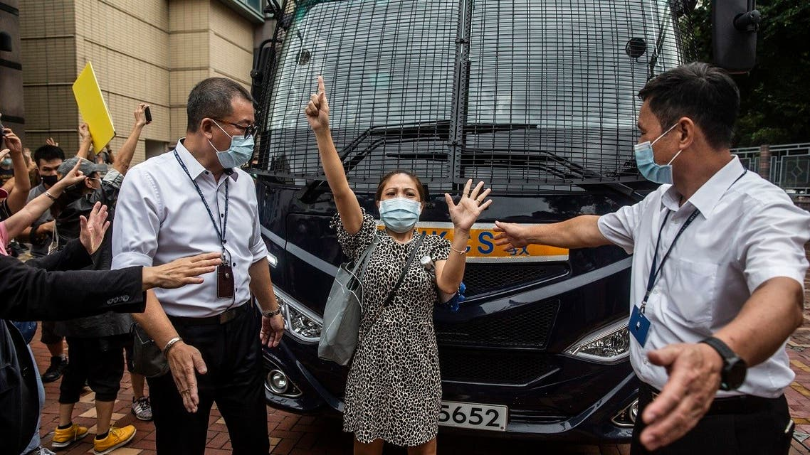 """A pro-democracy supporter (C) gestures """"five demands, not one less"""" as she blocks a prison van transporting democracy activist Tam Tak-chi after he was denied bail and charged with sedition at the Fanling magistrates court in Hong Kong on September 8, 2020. (AFP)"""