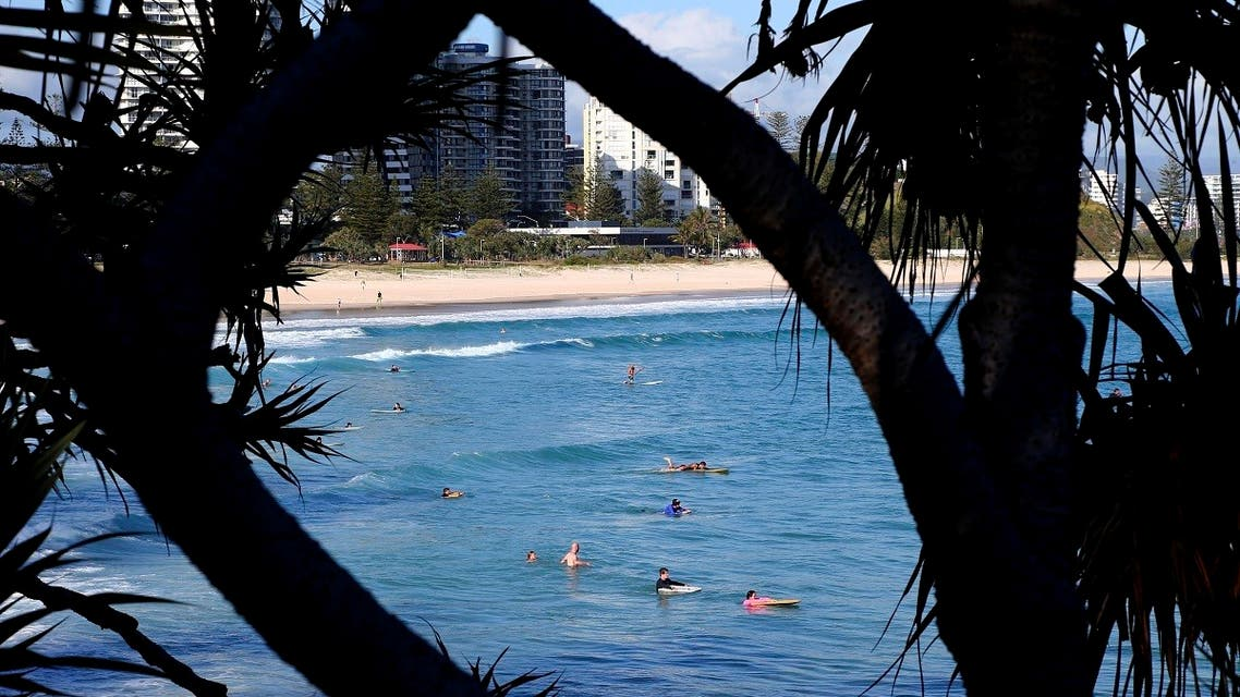 Surfers wade in the water waiting for waves off the Southern Gold Coast area of Greenmount Beach, Gold Coast. (AP)