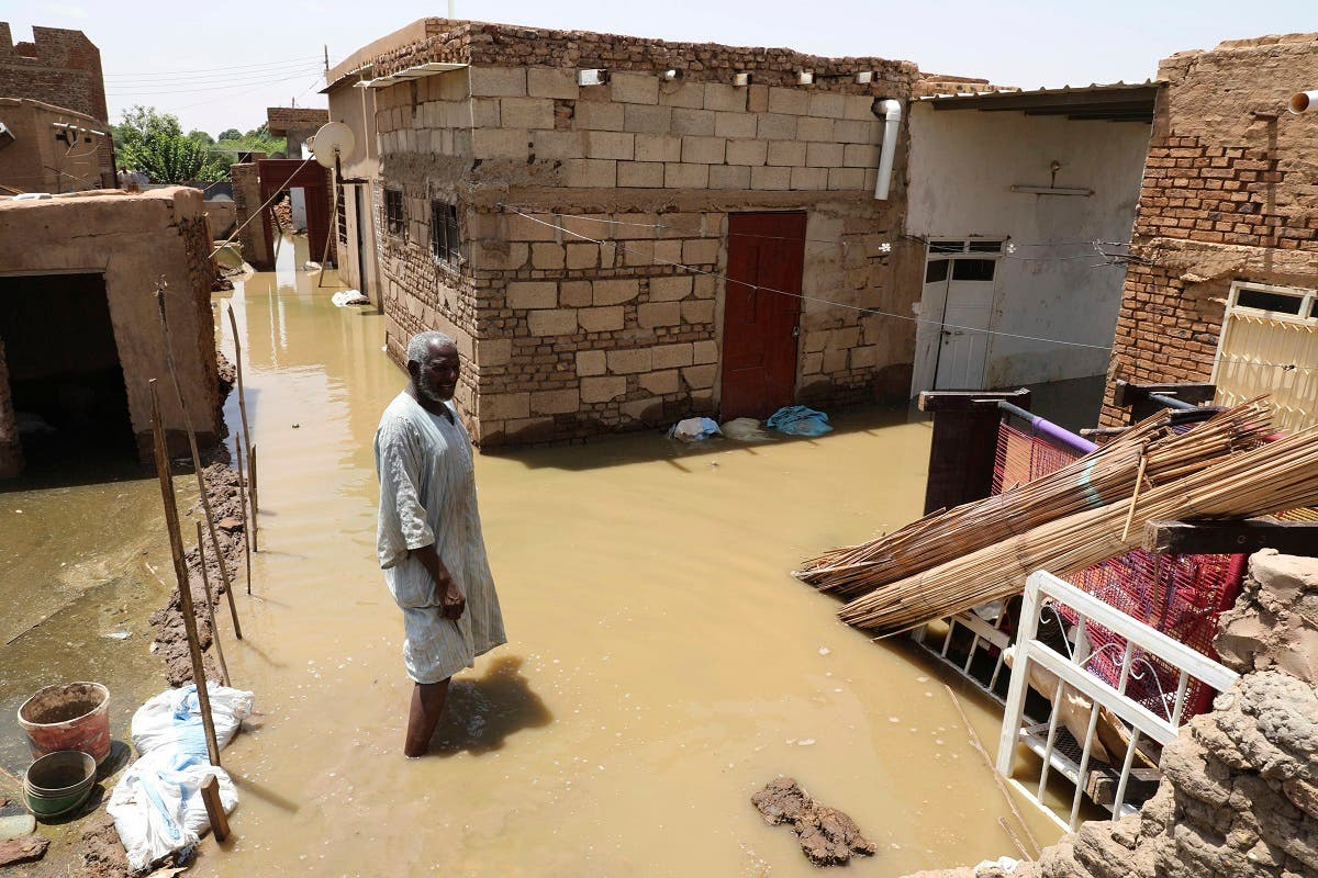 A man passes on the side of a flooded road in the town of Alkadro, about (20 km) north of the capital Khartoum, Sudan. (AP)