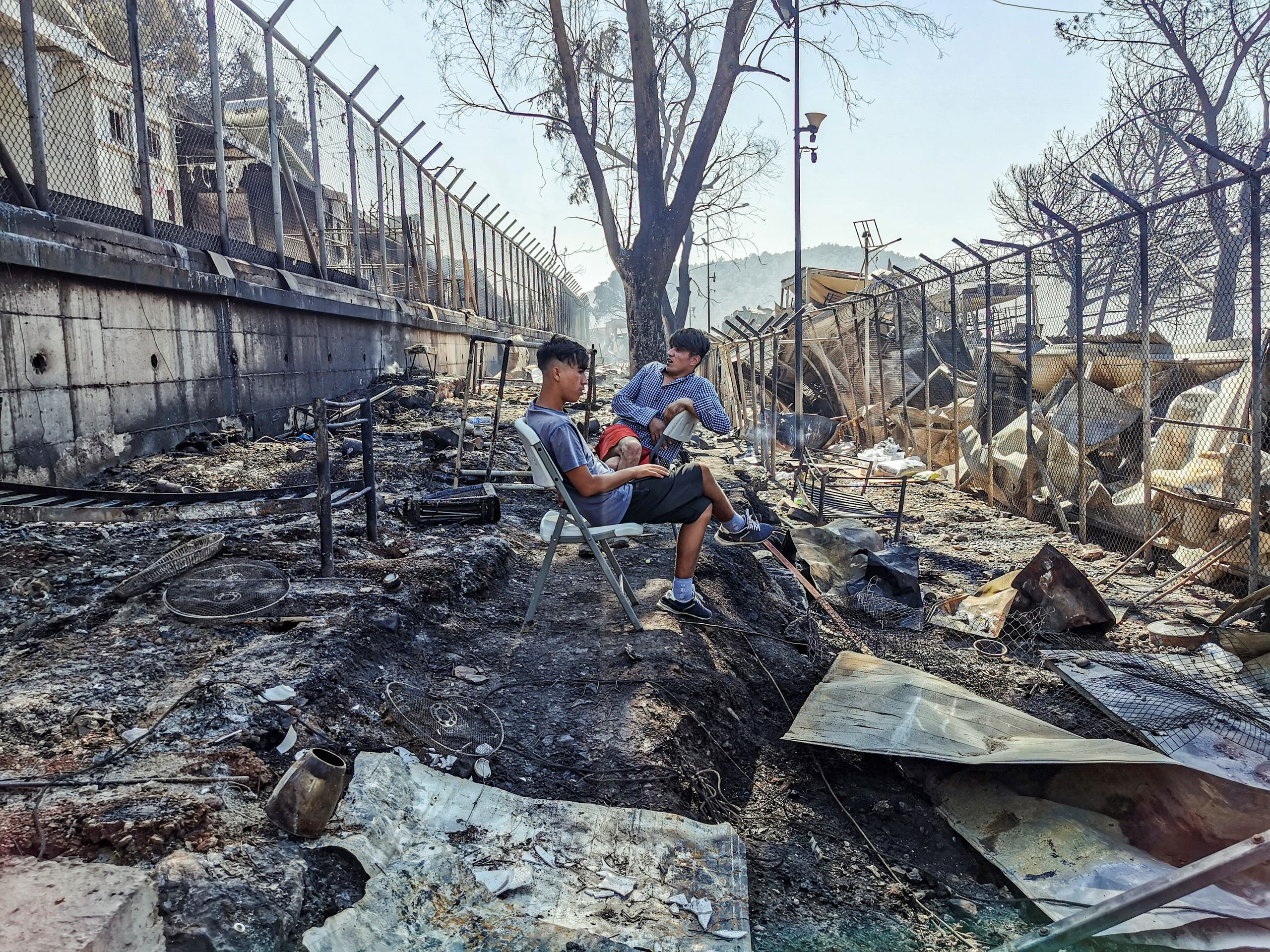 Migrants sit inside the burnt Moria Camp on the Greek island of Lesbos on September 9, 2020, after a major fire. (AFP)