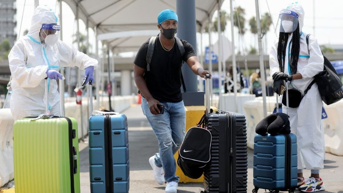 Air travelers (L and R) in personal protective equipment (PPE) at Los Angeles International Airport (LAX) amid the COVID-19 pandemic on August 20, 2020 in Los Angeles, California. (AFP)
