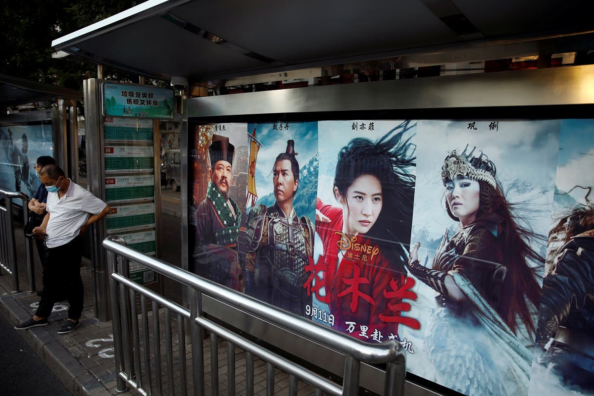 "People stand near an advertisement promoting Disney's movie ""Mulan"" at a bus stop in Beijing, China September 9, 2020. (Reuters)"