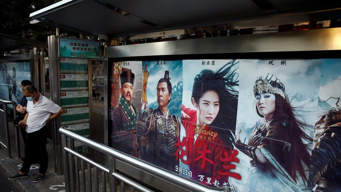"""People stand near an advertisement promoting Disney's movie """"Mulan"""" at a bus stop in Beijing, China September 9, 2020. (Reuters)"""