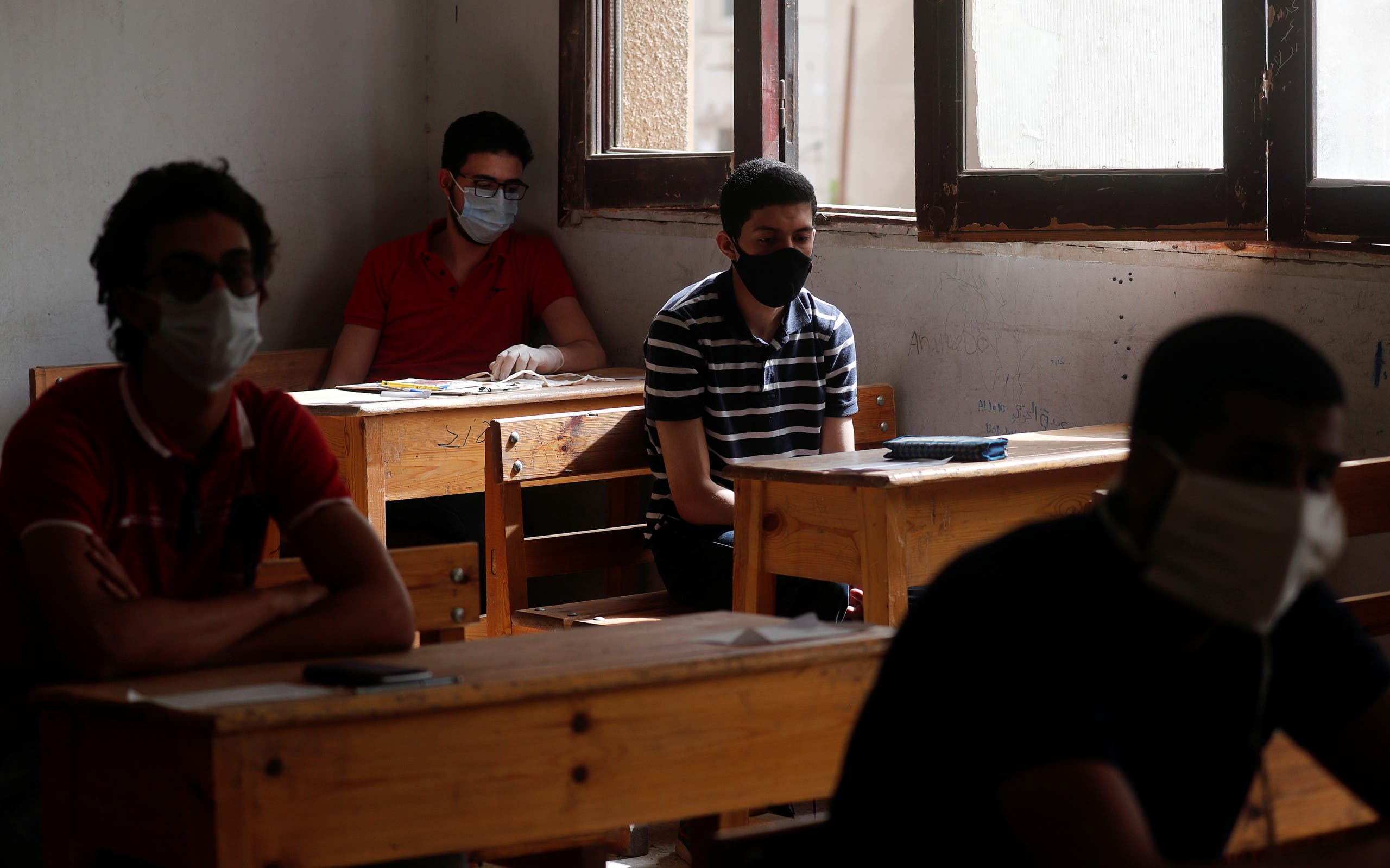 Egyptian high school students wear protective face masks as they attend the first day of final exams, amid concerns over the coronavirus disease (COVID-19) outbreak, in Cairo, Egypt June 21, 2020. (Reuters)