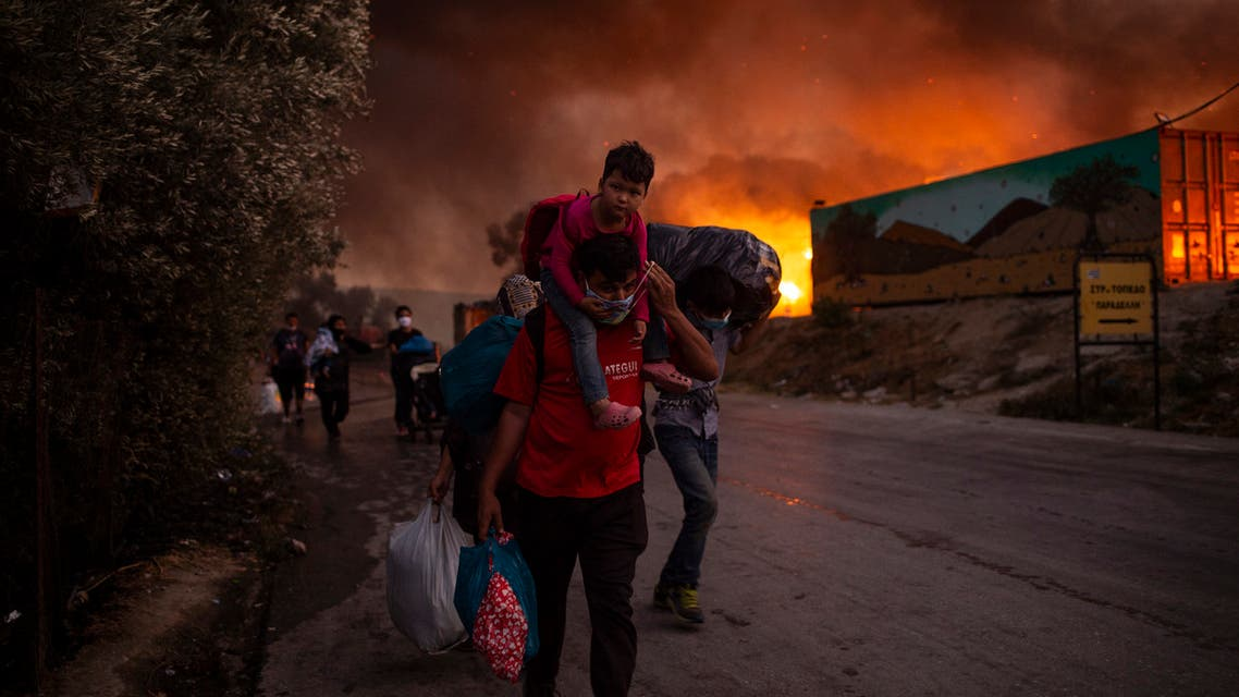 People with children flee flames after a major fire broke out in the Moria migrants camp on the Greek Aegean island of Lesbos. (AFP)