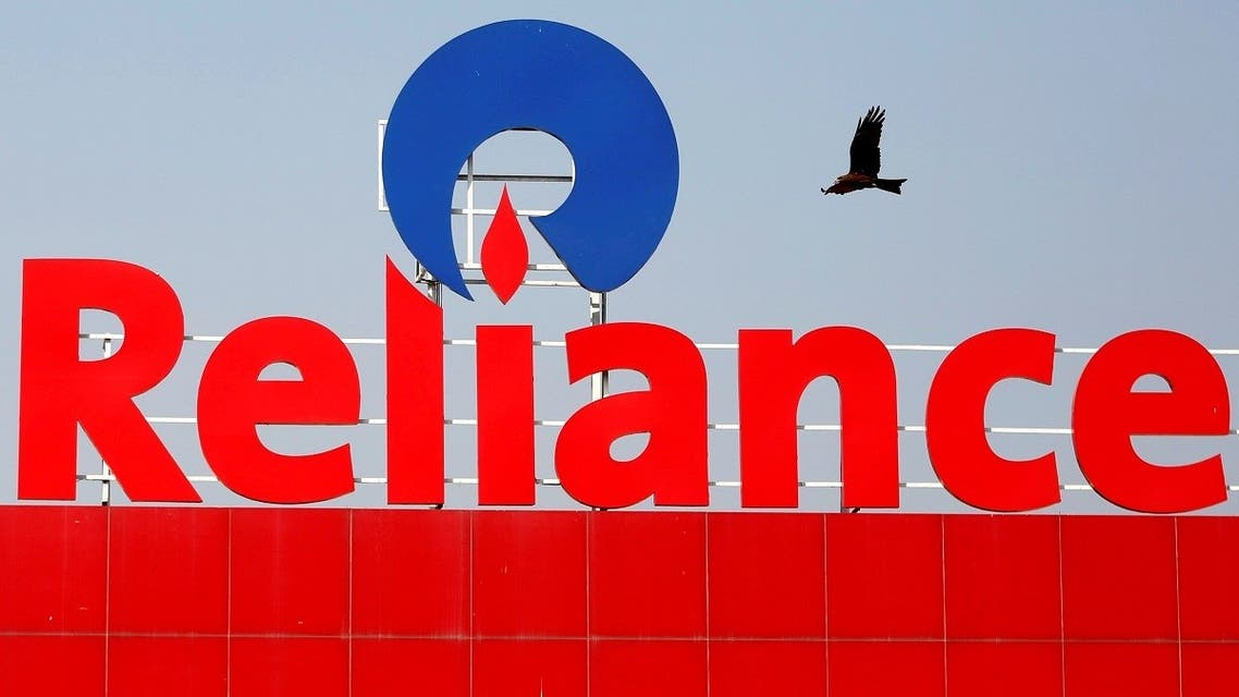 A bird flies past a Reliance Industries sign in Ahmedabad, India. (Reuters)