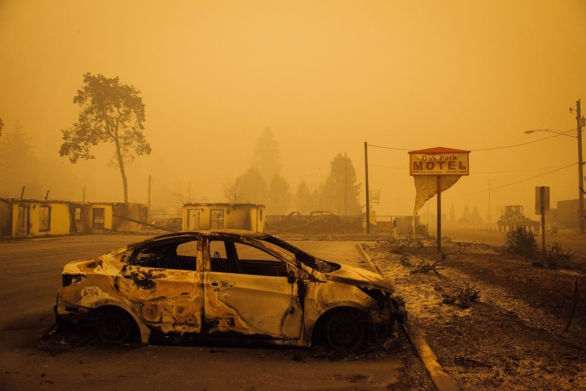 A charred vehicle is seen in the parking lot of the burned Oak Park Motel after the passage of the Santiam Fire in Gates, Oregon, on September 10, 2020. (AFP)
