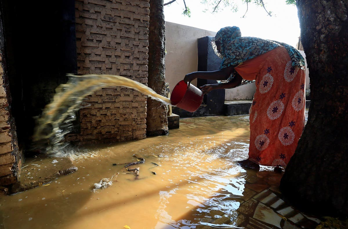 A resident pours out the waters of the Blue Nile floods from her backyard within the Al-Ikmayr area of Omdurman in Khartoum, Sudan. (Reuters)