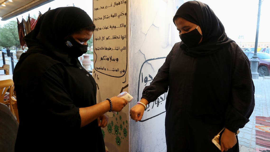 A restaurant's female member of the security personnel wearing a protective face mask, following the outbreak of the coronavirus disease (COVID-19), checks the temperature of a woman before enter the restaurant after reopened, in Riyadh, Saudi Arabia June 13, 2020. Picture taken June 13, 2020. REUTERS/Ahmed Yosri