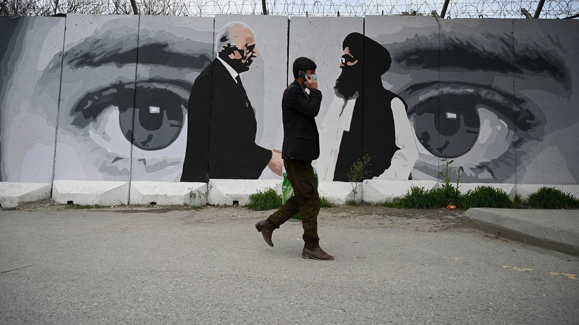 A man wearing a facemask as a precautionary measure against the COVID-19 novel coronavirus walk past a wall painted with images of US Special Representative for Afghanistan Reconciliation Zalmay Khalilzad (L) and Taliban co-founder Mullah Abdul Ghani Baradar (R), in Kabul. (AFP)