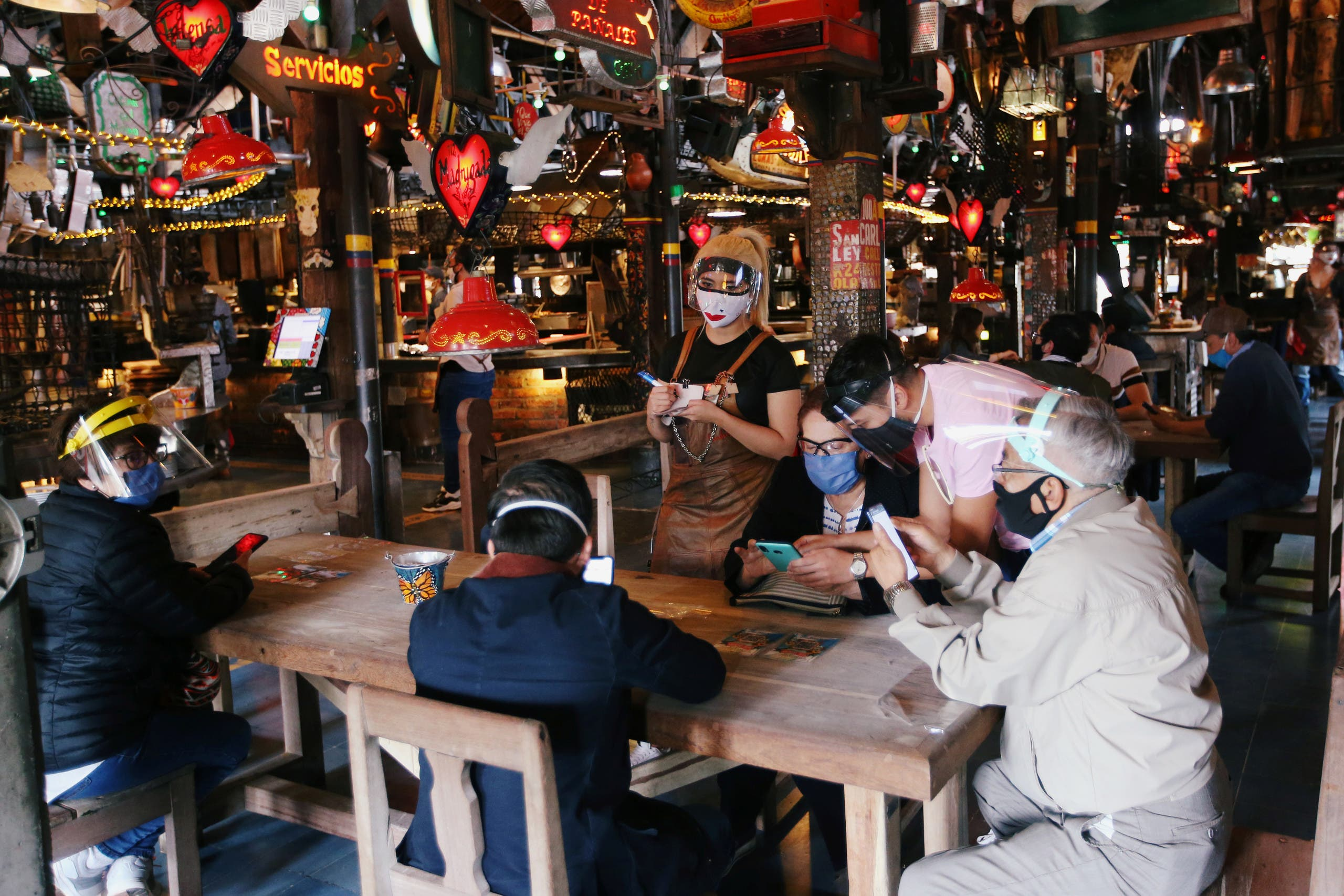 Customers wearing protective masks talk to a waiter at the Andres Carne de Res restaurant, amidst the coronavirus disease (COVID-19) outbreak, in Chia, (Reuters)