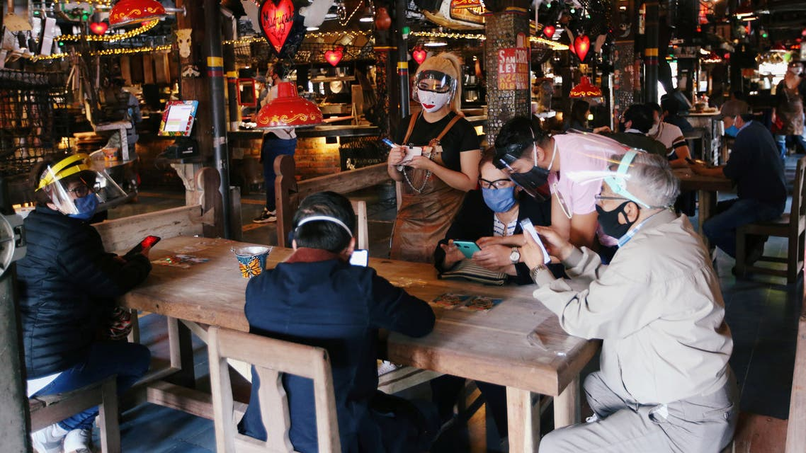 Customers wearing protective masks talk to a waiter at the Andres Carne de Res restaurant, amidst the coronavirus disease (COVID-19) outbreak, in Chia, Colombia August 30, 2020. Picture taken August 30, 2020. REUTERS/Luisa Gonzalez
