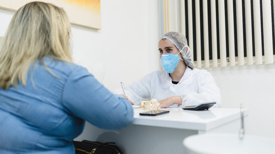 Covid19: Female doctor attending a patient in the office stock photo