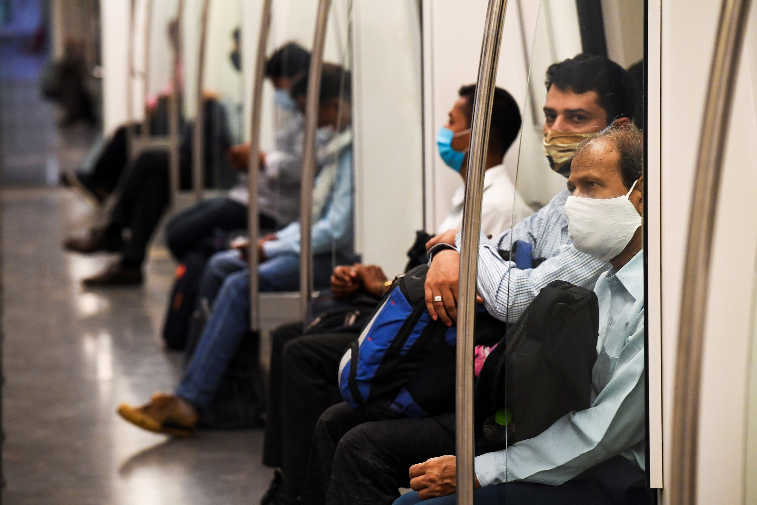 مسافرون في مترو بالهند يضعون كمامات للوقاية من كورونا