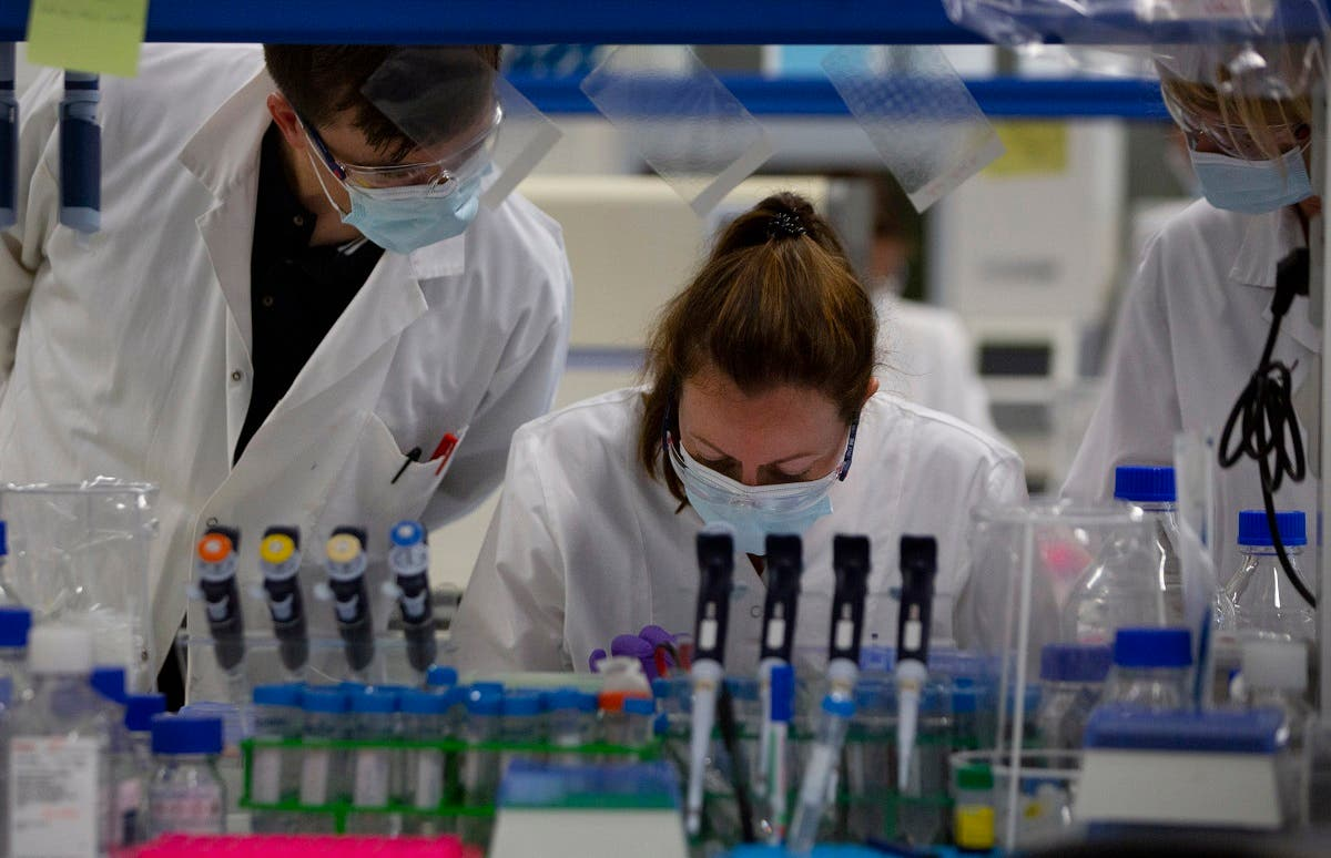 Lab technicians speak with each other during research on coronavirus, COVID-19, at Johnson & Johnson subsidiary Janssen Pharmaceutical in Beerse, Belgium. (AP)