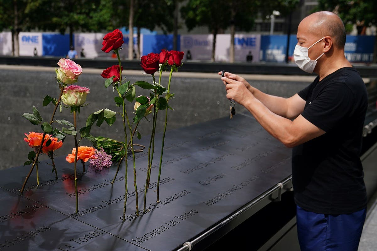A man takes photos of flowers sitting in names at the north reflecting pool at the National 9/11 Memorial the day before the 19th anniversary of attacks in the Manhattan borough of New York City, New York, US. (Reuters)