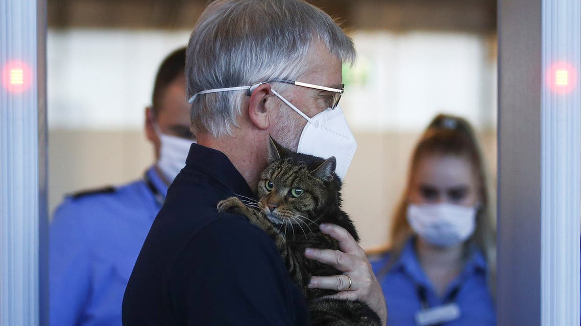 A man carrying a cat walks past security control at the Vienna International Airport in Schwechat, Austria July 1, 2020. REUTERS/Lisi Niesner