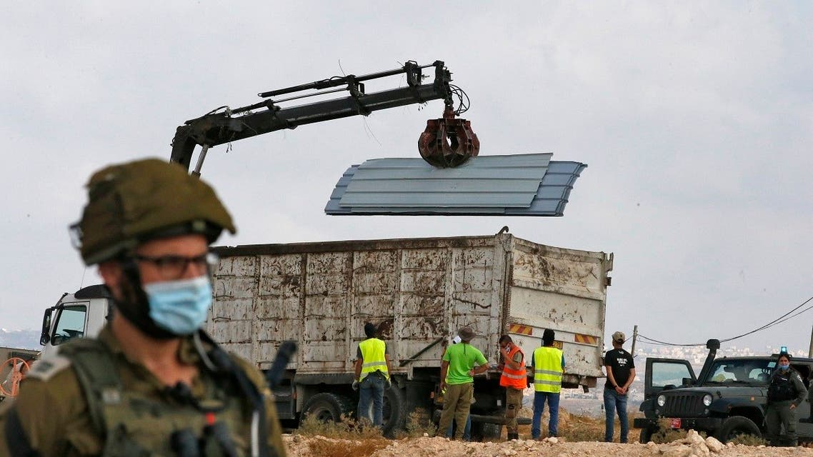 Israeli soldiers and border police gather as a structure serving as a home to a Palestinian family is demolished in the village of Susya south Yatta in the southern West Bank. (AFP)