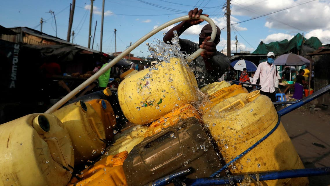 A vendor fills jerrycans with water for sale, amid a water shortage during the coronavirus disease (COVID-19) outbreak, in Nairobi, Kenya May 13, 2020. Picture taken May 13, 2020. REUTERS/Njeri Mwangi TPX IMAGES OF THE DAY