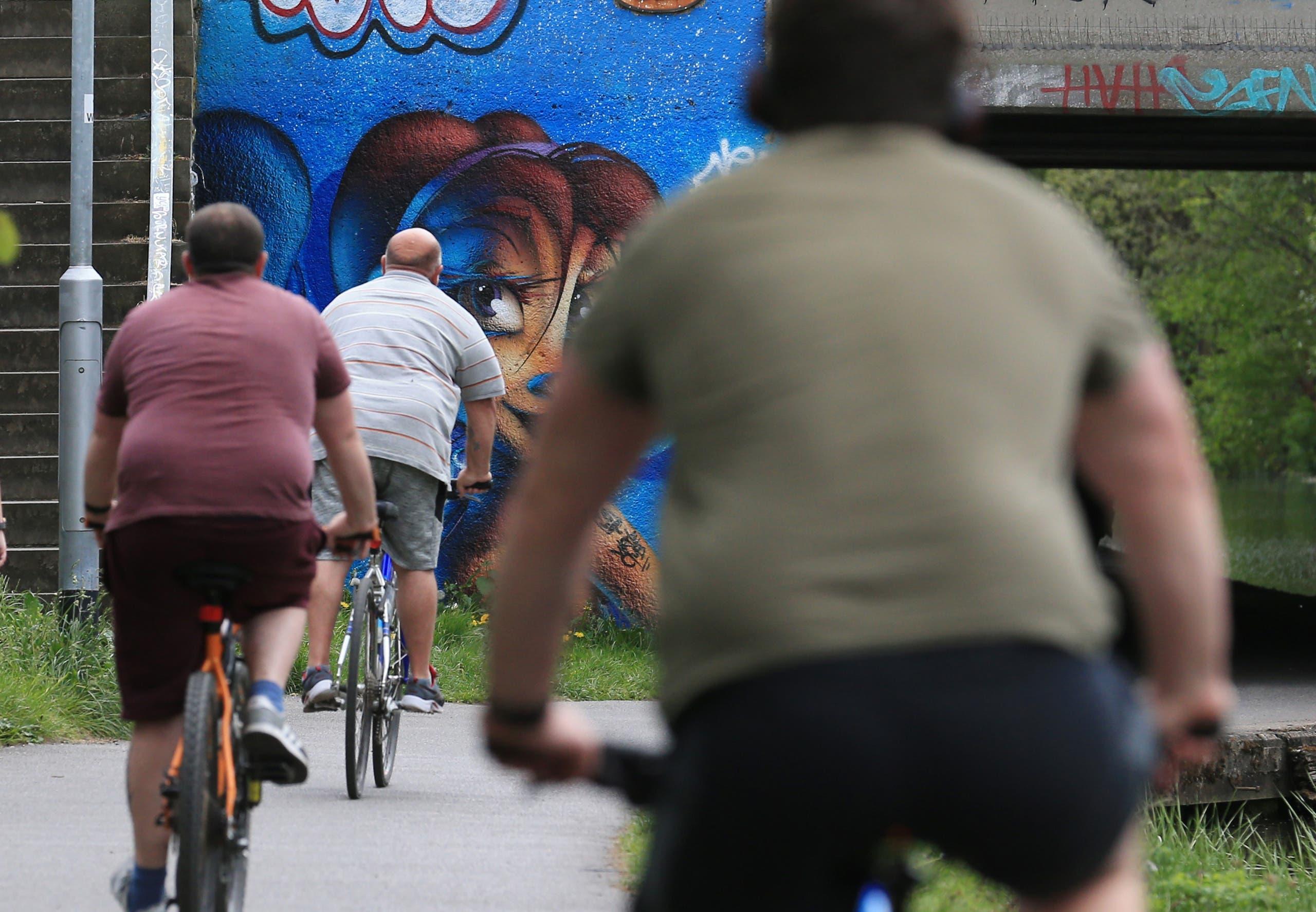 رجال يعانون من البدانة يماسرون ركوب الدراجات خلال الإغلاق في مايو الماضي في انكلترا