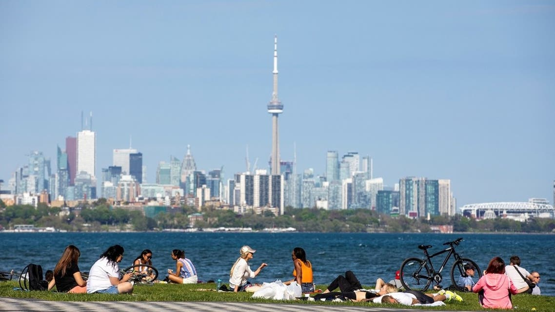 People maintain social distance as they sit at Humber Bay Shores park, Ontario, Canada May 24, 2020. (Reuters)