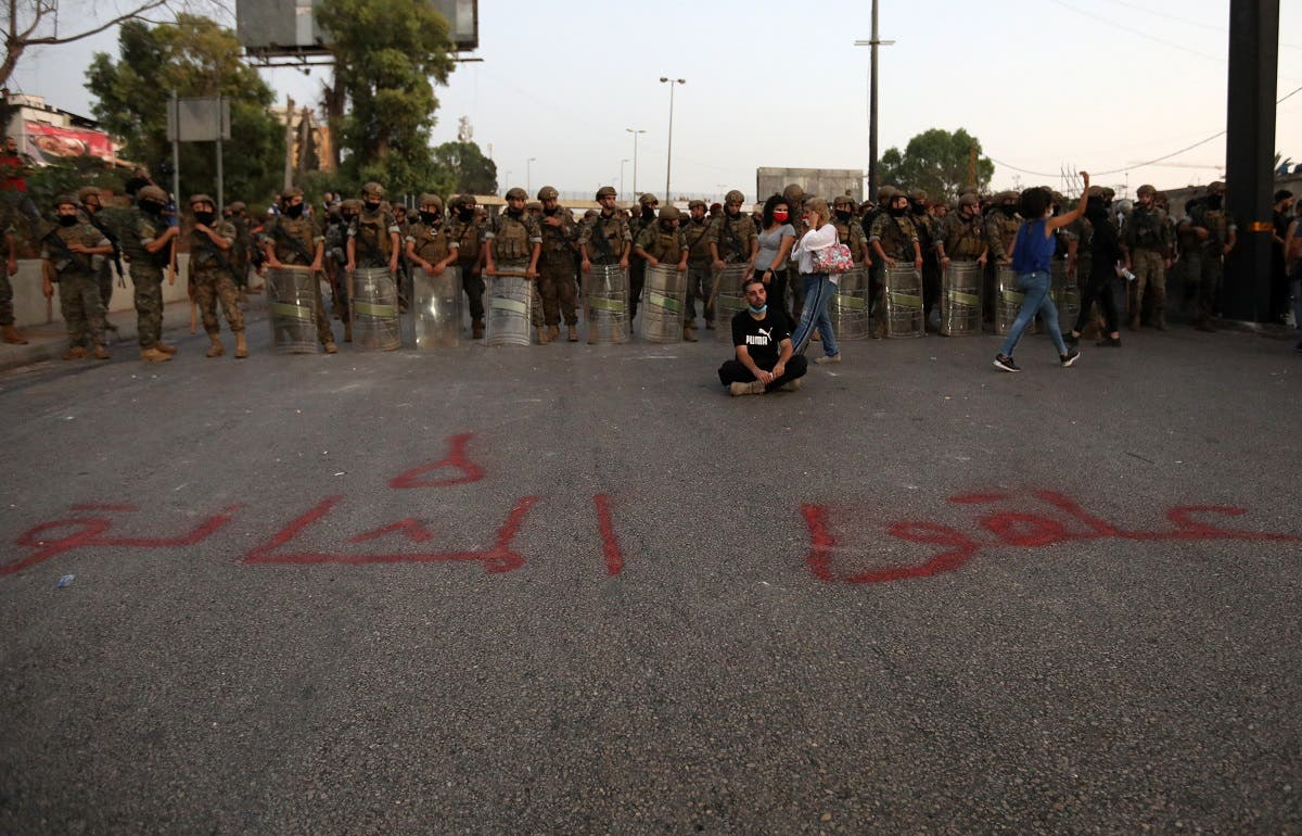 A Lebanese anti-government protester sits in front writing on the ground in Arabic that reads prepare the gallows during a demonstration against the lack of progress in a probe by authorities into a monster blast that ravaged swathes of the capital 40 days ago. (AFP)