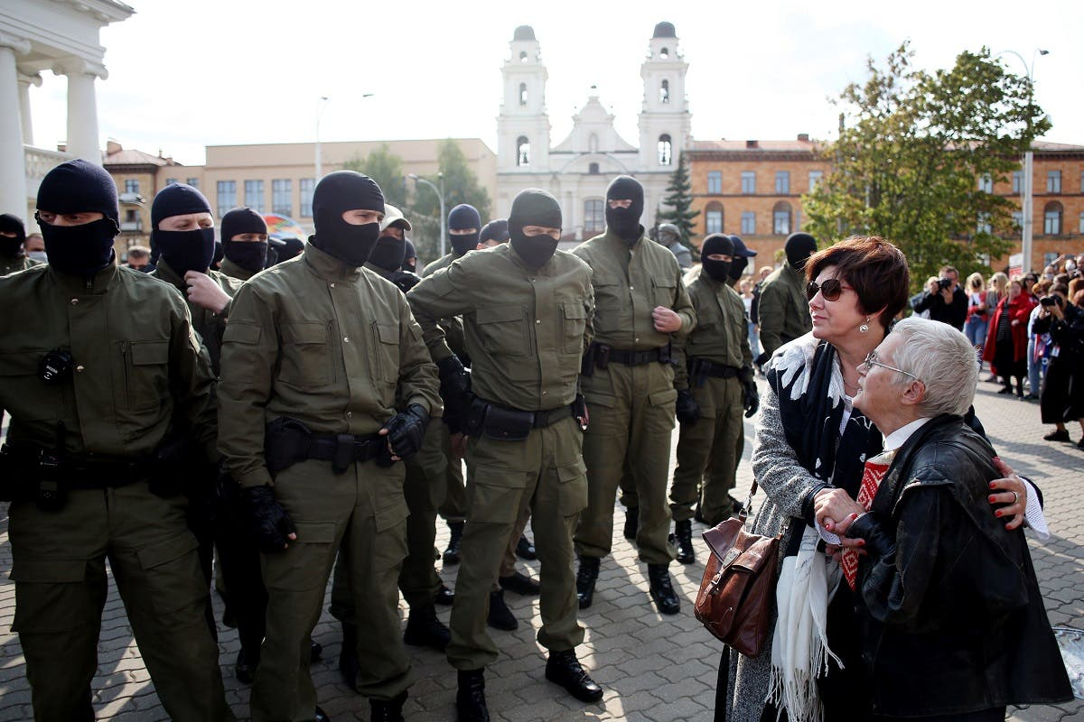 Opposition activist Nina Baginskaya (R), 73-year-old, and an unidentified woman stand in front of Belarus riot police officers during a rally in Minsk on September 12, 2020. (AFP)