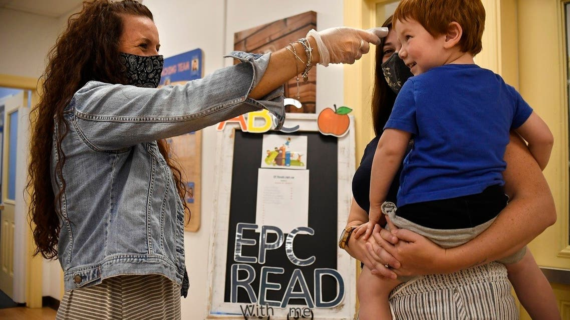 A daycare director takes the temperature of a child held by his mother in Connecticut, Aug. 27, 2020. (AP)