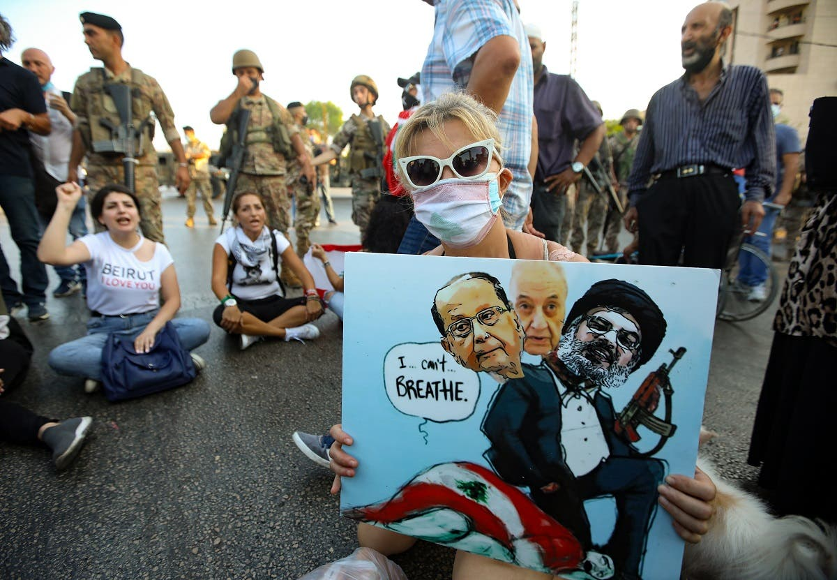 A Lebanese anti government protester holds a placard with a cartoon of (L-R) President Michel Aoun, Parliament Speaker Nabih Berri and head of the Shiite movement Hezbollah Hassan Nasrallah sitting atop a national flag (with writing that refers to George Floyd's death) during a demonstration against the lack of progress in a probe by authorities into a monster blast that ravaged swathes of the capital 40 days ago, near the presidential palace in Baabda. (AFP)
