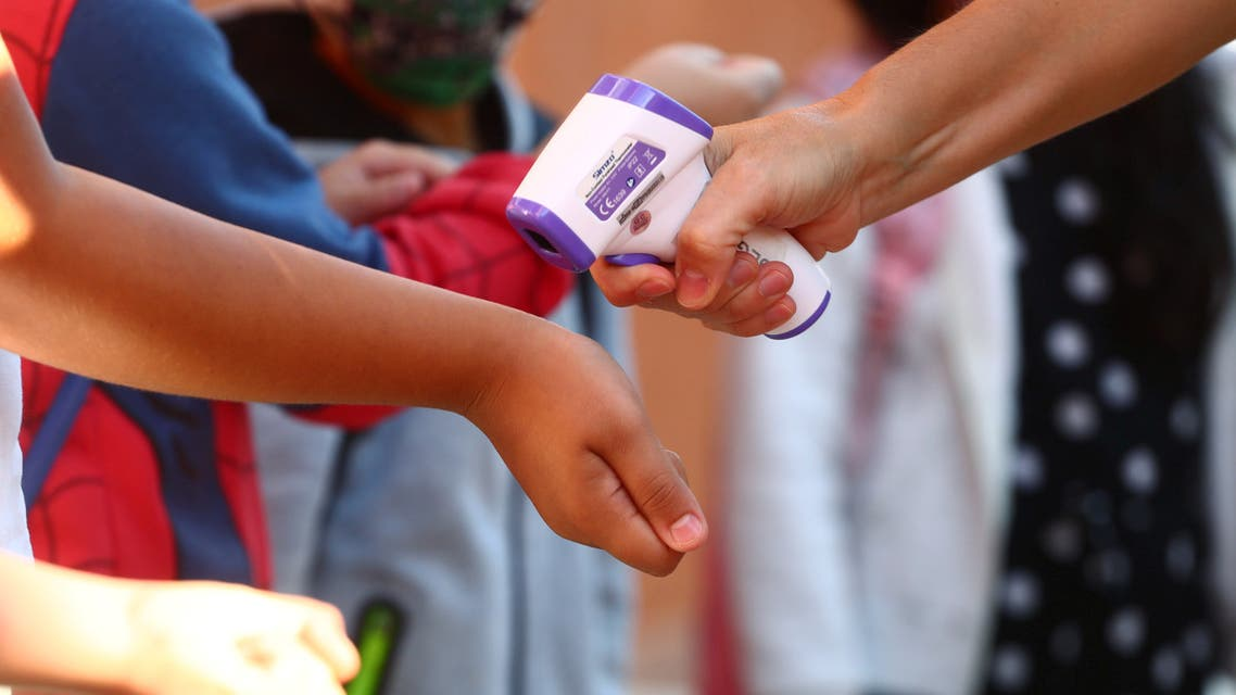Pupils have their temperature checked before entering on the first day of school amid the coronavirus disease (COVID-19) outbreak in Madrid. (Reuters)