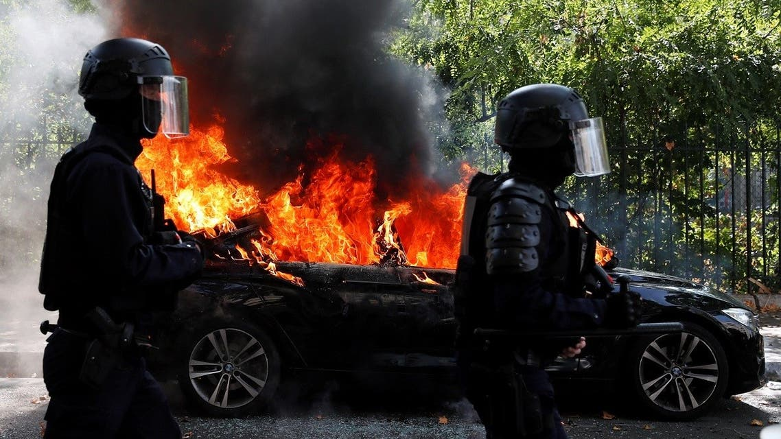 French CRS riot police officers walk past a burning car during a demonstration of the yellow vests movement in Paris. (Reuters)