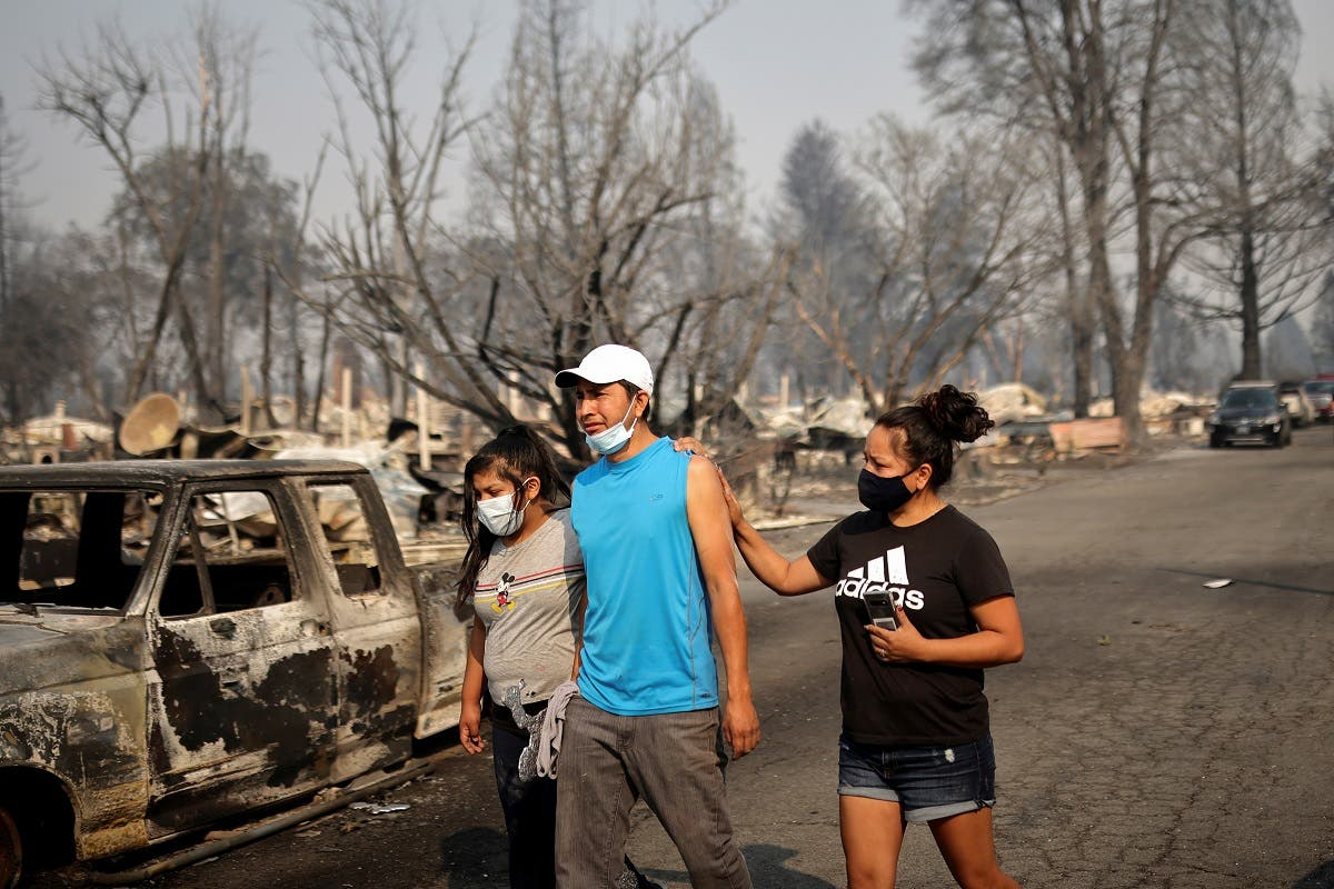 Sandra and Daniela Reyes comfort Isaias Reyes while visiting their damaged trailer home after the wildfires destroyed a neighborhood in Bear Creek, Phoenix, Oregon, U.S., September 10, 2020. REUTERS_168242335_RC24WI945JEW_RTRMADP_3_USA-WILDFIRES