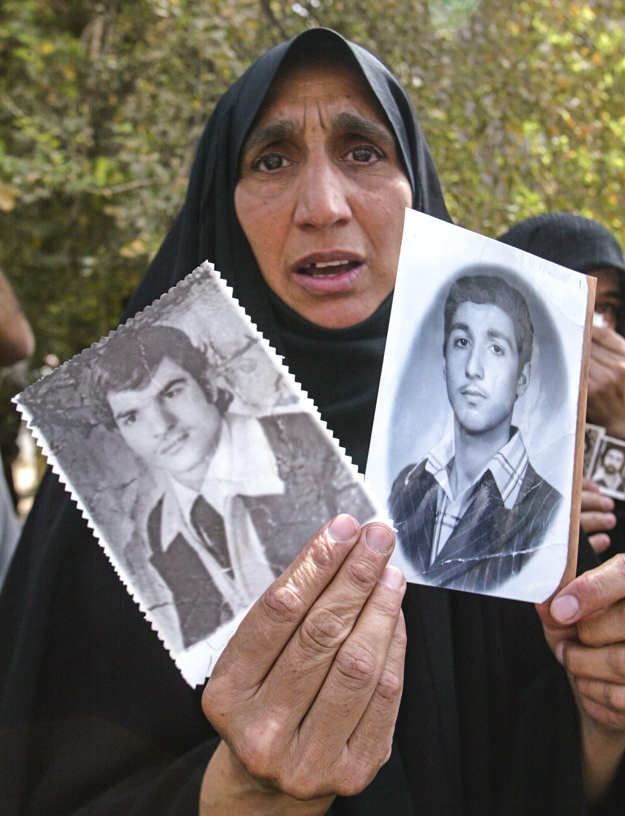 سيدة عراقية تحمل صورة أقارب لها فقدوا خلال عهد البعث في العراق (أرشيفية- فرانس برس)