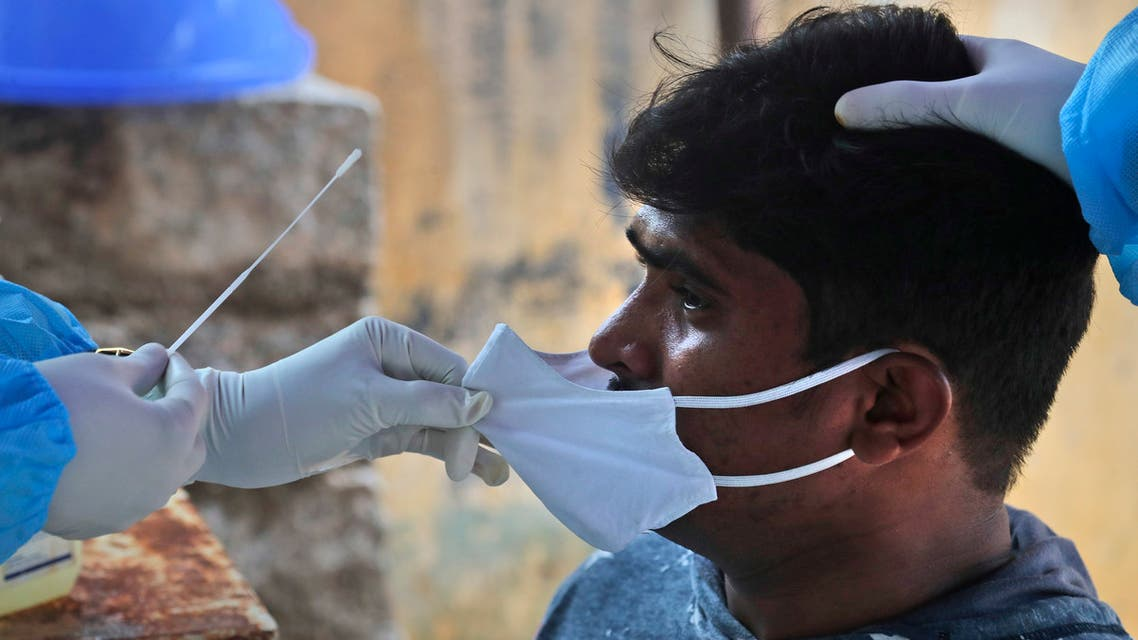 A health worker takes a nasal swab sample to test for COVID-19 in Hyderabad, India, Sunday, Sept. 13, 2020. (AP)