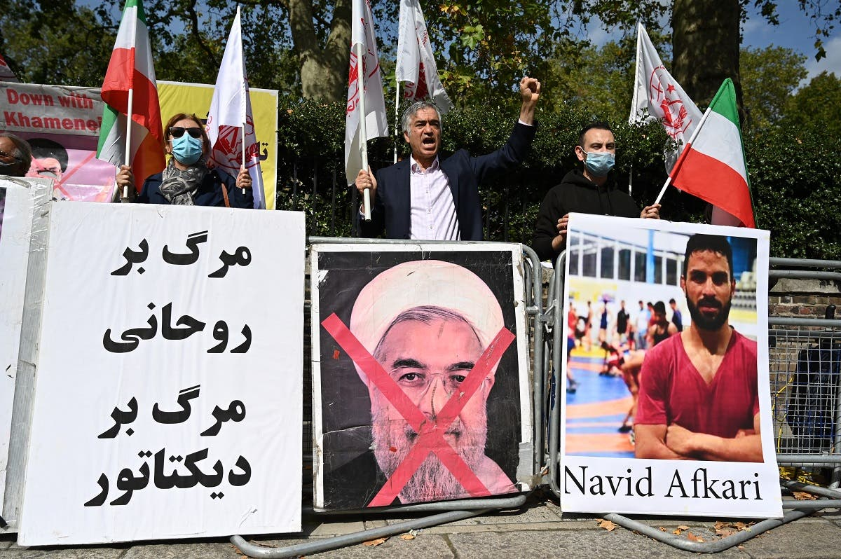 Protesters wave the Lion and Sun flag of the National Council of Resistance of Iran and the white flag of the People's Mujahedin of Iran, two Iranian opposition groups, with a placard depicting the crossed out face of Iran's President Hassan Rouhani as they demonstrate outside the Iranian embassy in London on September 12, 2020 against the execution of Iranian wrestler Navid Afkari. (AFP)