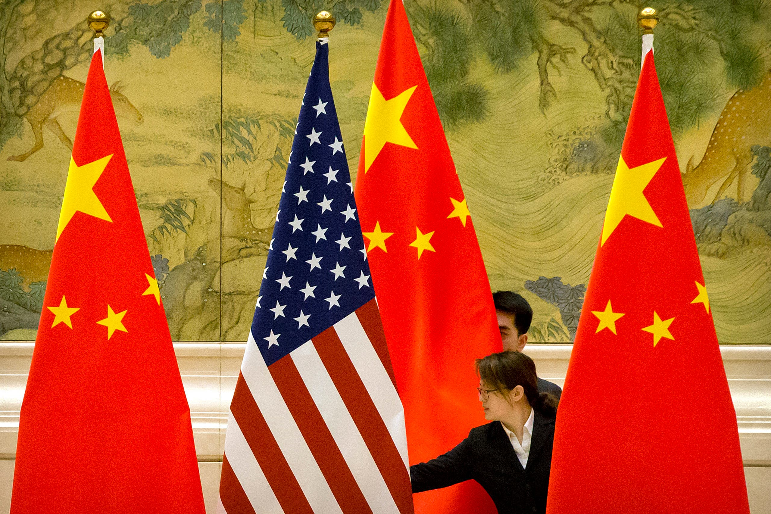 Chinese staff adjust US and Chinese flags before the opening session of trade negotiations between US and Chinese trade representatives at the Diaoyutai State Guesthouse in Beijing on February 14, 2019. (AFP)