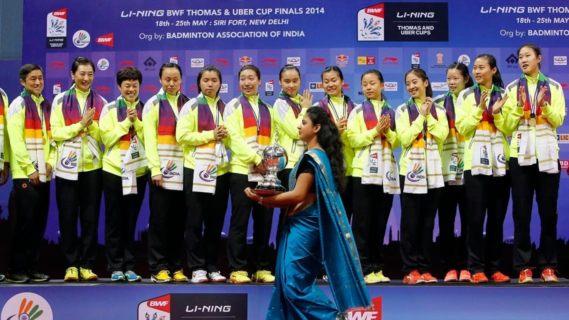 2014-05-24An Indian host carries the Uber Cup badminton championship trophy as she walks past the China's team members waiting to receive the trophy after their win in New Delhi May 24, 2014. REUTERST120000Z_99292521_GM1EA5P01LN01_RTRMADP_3_BADMINTON-THOMAS