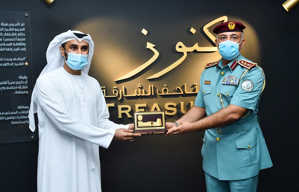 Nasir Al Darmaki. Museums Strategic Planning Department Manager - SMA, exchanges a memento with an official of the Sharjah Police. (Courtesy: SMA)
