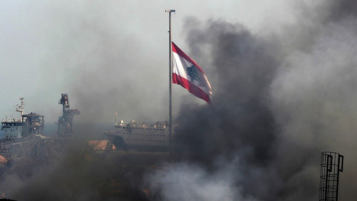 A Lebanese flag flutters amid billowing smoke as firefighters (unseen) extinguish the remaining flames at the seaport of Beirut, on September 11, 2020, a day after a huge fire erupted in harbour warehouses. (AFP)