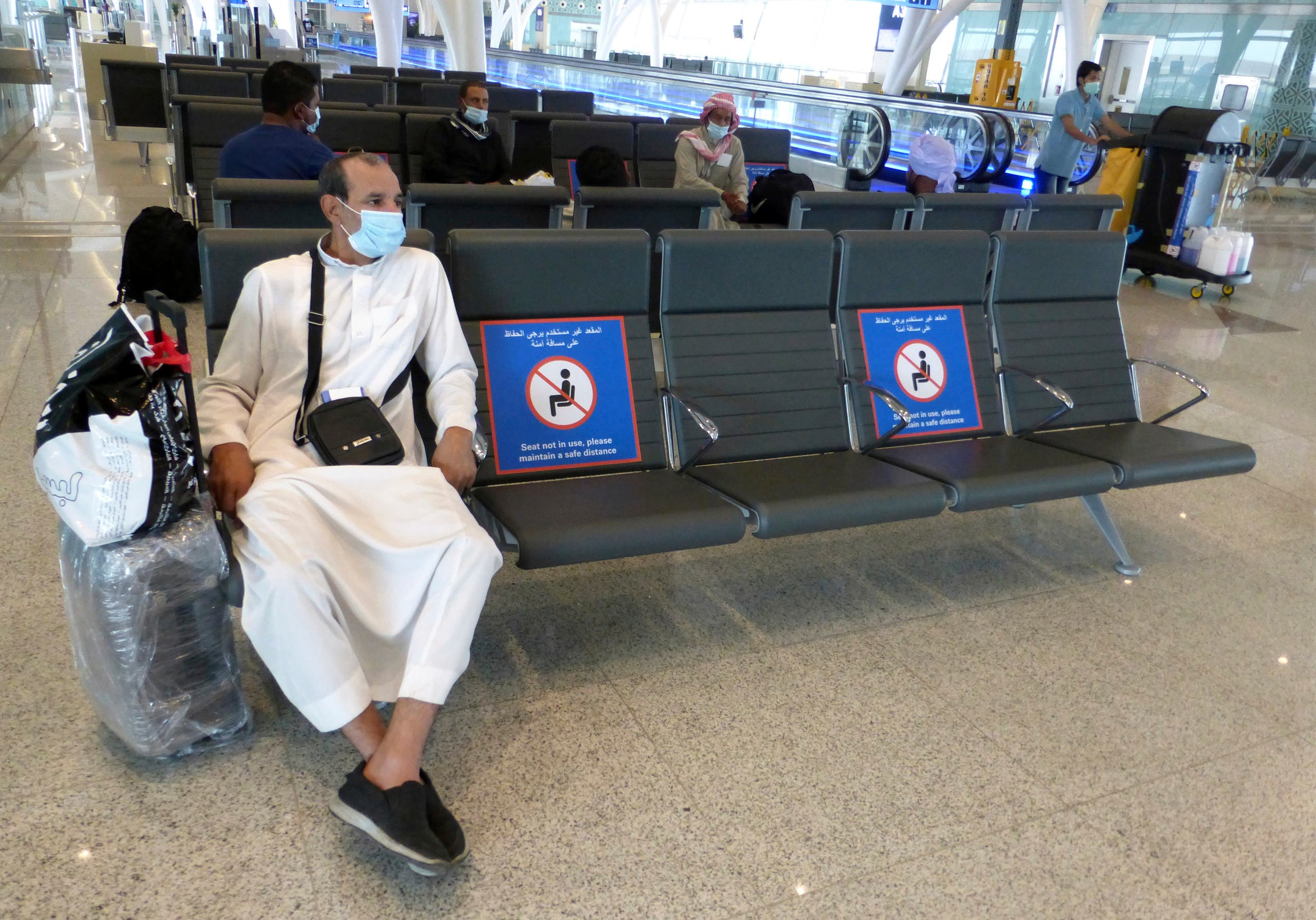 A passenger sits beside posters displaying social distancing restrictions as he waits for his flight at the King Abdulaziz International Airport. (File photo: AP)