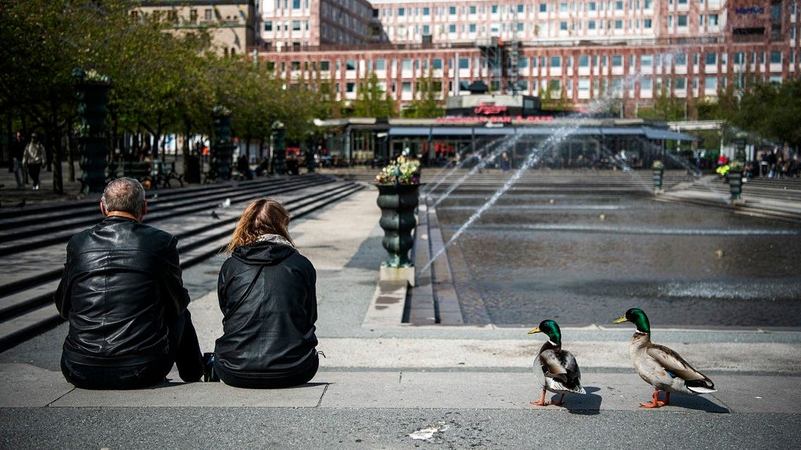 Two ducks stand next to a couple as they enjoy the warm weather at the Kungstradgarden in Stockholm on May 8, 2020, amid the new coronavirus COVID-19 pandemic. (AFP)